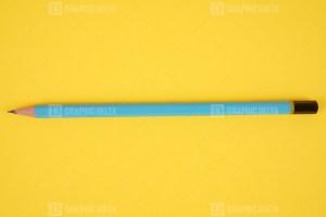 Blue pencil on yellow stock photo