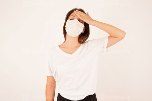 Woman in medical mask suffering from headache