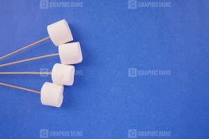 White marshmallows with sticks on blue background