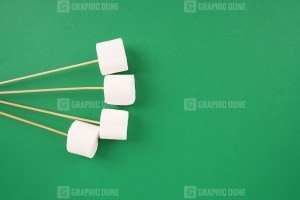 White marshmallows with sticks on green background