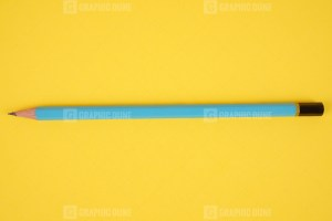 Blue pencil on yellow stock photo