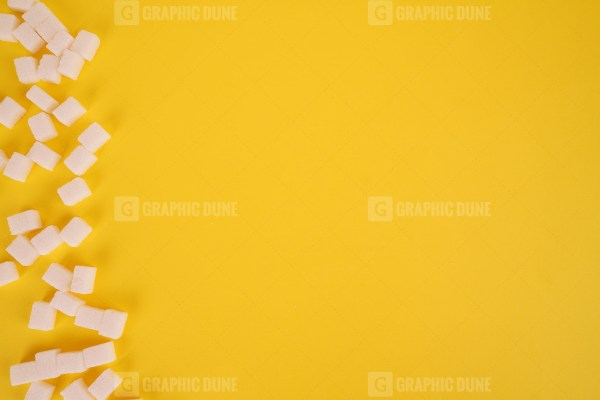 Cube sugar on yellow background stock photo