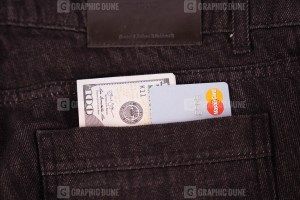 Mastercard and dollars in jeans pocket