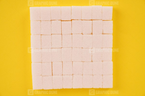 Stack of cube sugar on yellow background