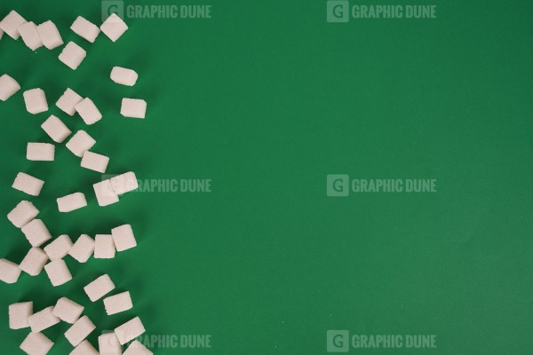 Sugar cubes on green stock image