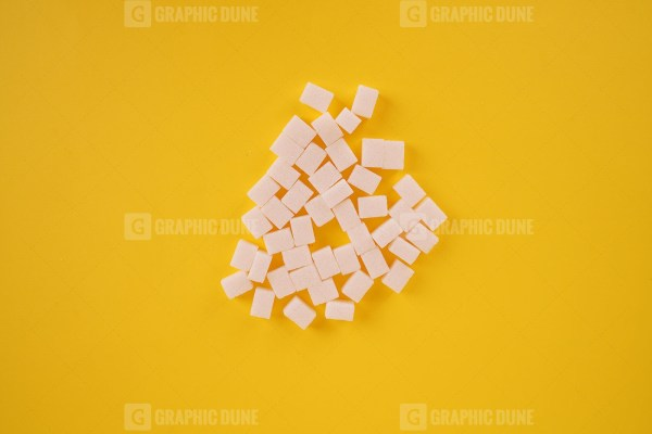 Sugar cubes on yellow background stock photo