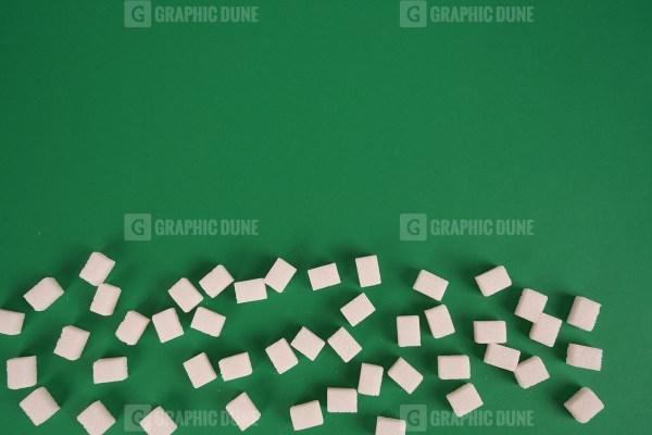 White sugar on green background
