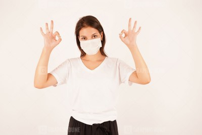 Girl in a medical mask shows OK