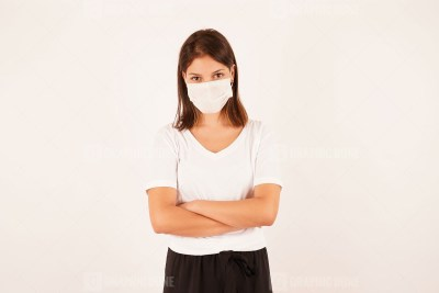 Young woman in medical mask with crossed arms