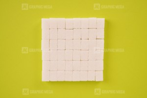 Stack of cube sugar on bright green background