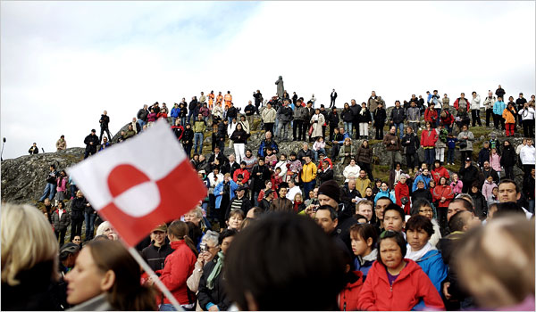 Crowd of Greenlanders on a hill, with one in the foreground waving a Greenland flag.