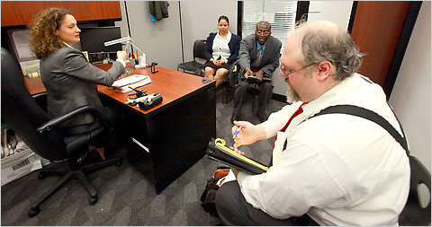 Barbara Felska, an immigration officer, with a video recorder on her desk, meets with one couple, Sally Bines and Yusuf Mohammed, and their lawyer, Daniel Lundy.