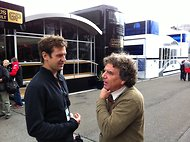 Derek Hill, left, speaks with Paul-Henri Cahier, a photographer, in the paddock at the Belgian Grand Prix last weekend.