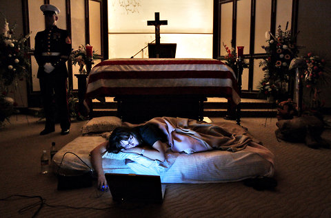 The photo, taken by New York Times's Todd Heisler, while he was a staff photographer at Rocky Mountain News in 2005. The night before the burial of her husband's body, Katherine Cathey refused to leave the casket, asking to sleep next to his body for the last time. The Marines made a bed for her.