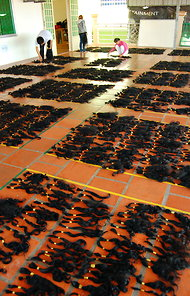On the rooftop of Arjuni, a hair company in Cambodia, workers begin sorting the natural-grown hair according to length and quality.