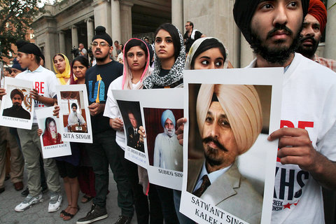 """Amritpal Singh of Queens, right, and others held up images of the victims, including an injured police officer, of the recent shooting at a Sikh temple in Oak Creek, Wis., as they took part in a vigil Wednesday (August 8) in Union Square Park."" (source: New York Times)"