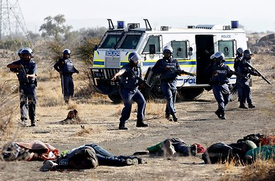 Police officers surround the bodies of miners after opening fire on a crowd at the Lonmin platinum mine in South Africa on Thursday.