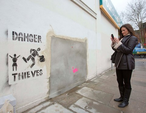 The original site of the Banksy work, with a warning added after its removal.