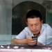 A man using a smartphone in Beijing. In China, Internet use is surging and smartphone providers are proliferating.