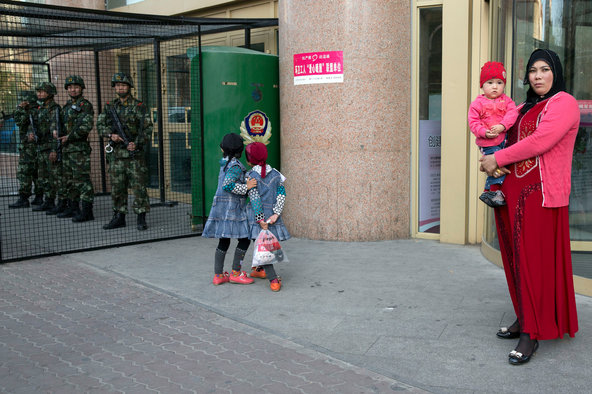 Uighur children playing on Thursday near a cage that protects heavily armed paramilitary police officers in Urumqi, the regional capital of Xinjiang.