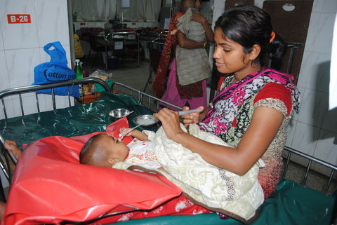 A young mother treats her baby with oral rehydration solution at the ICDDR,B hospital in Dhaka.