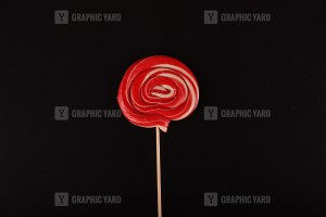 Red round lollipop isolated on black background