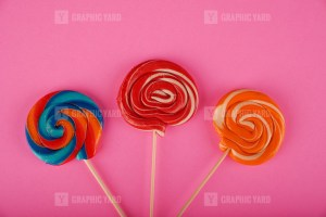 Spiral colored round lollipops on pink background