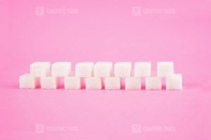 Cubes of sugar on pink background