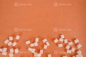 Lump sugar on orange stock photo