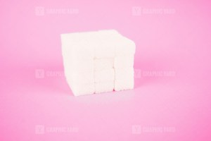 White sugar cube on pink background