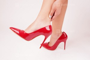 Woman having pain after wearing high heeled shoes