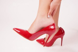 Woman holding painful sprained ankle