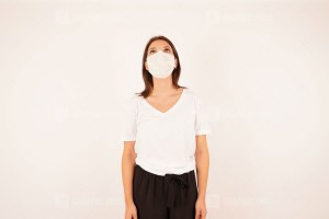 Woman in medical mask looking up