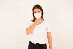 Woman in medical mask touching neck