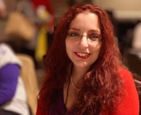 A photo of Amy Gravino at an event, wearing a red shirt, glasses, and smiling at the camera.
