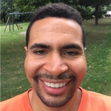 A close-up photo of Emmanuel Frowner wearing a orange shirt and standing in a park.