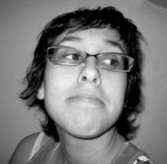 A black and white photo of Nadya G looking away from the camera. She has a slight smile and is wearing glasses.