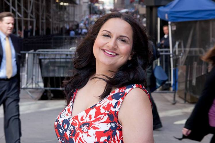 A head shot photo of Sonia Chand standing on a busy city street. She is smiling and wearing a red flower pattern dress.