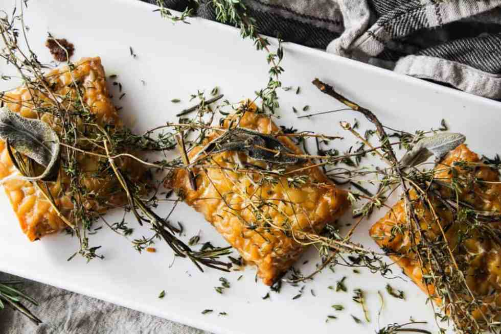 This simple recipe for herb baked tempeh is a flavorful entree that's wholly worthy of a coveted spot on your holiday table. Plant-based holiday recipe!