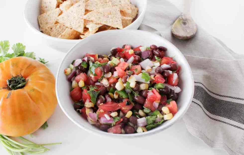This fresh black bean salsa is made with fresh heirloom tomatoes and grilled sweet corn for a healthy appetizer or snack that'll be a party favorite.