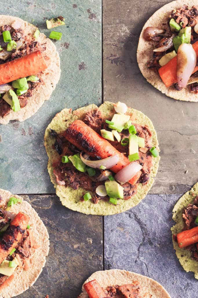 These easy roasted carrot tacos are bursting with delicious umami flavor from soy sauce. Slathered with a zesty black bean lime spread! Vegan/Plant-Based!