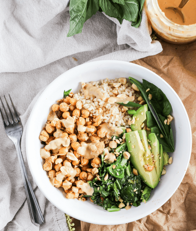 Chickpea bowls served with spicy peanut sauce and seasonal sesame oil greens for the delicious flavors of Thai take-out from home. Easy plant-based recipe!