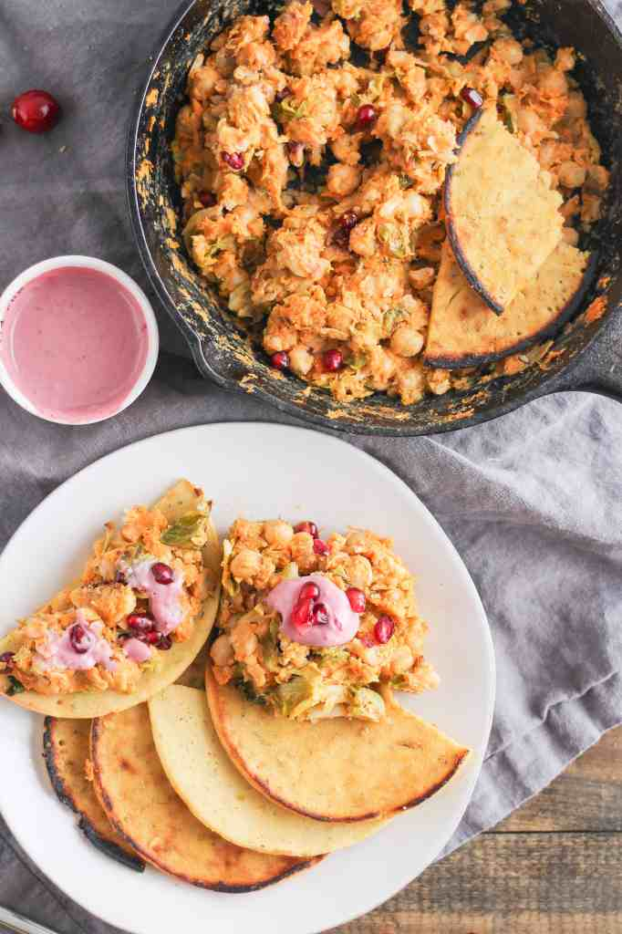 This fall-inspired chickpea scramble is the best way to use leftover roasted veggies and cranberry sauce from your Thanksgiving dinner. Serve the scramble on a piece of homemade socca flatbread for a festive start to the holiday season!
