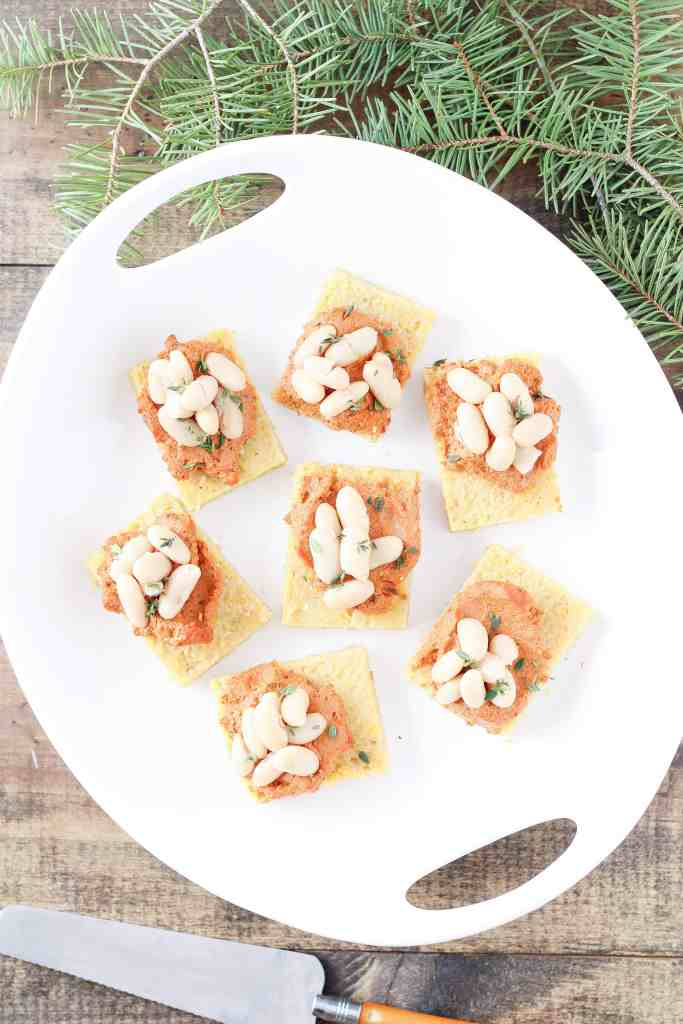 Cannellini Bean Polenta Squares are a festive (and completely vegan) appetizer for the holidays and beyond. Guests will love this delicious bite of polenta (Italian grits) smothered in roasted red pepper and sun-dried tomato bean and walnut spread.