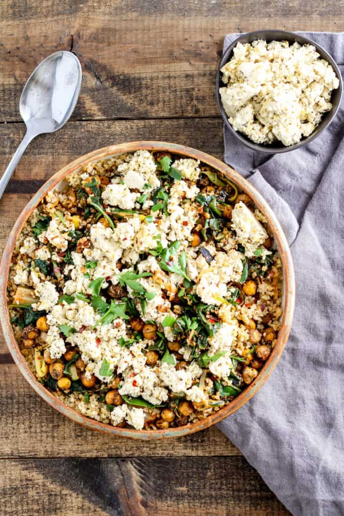 Comforting and delicious Greek roasted chickpeas served with vegan tofu feta, spicy greens, and freekeh. You need this dinner in your weeknight rotation!