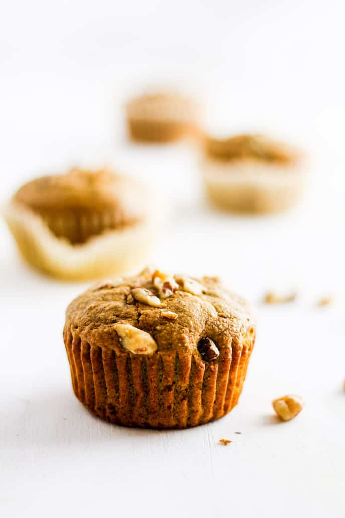 Straight on shot of gluten-free golden milk muffin against white backdrop.