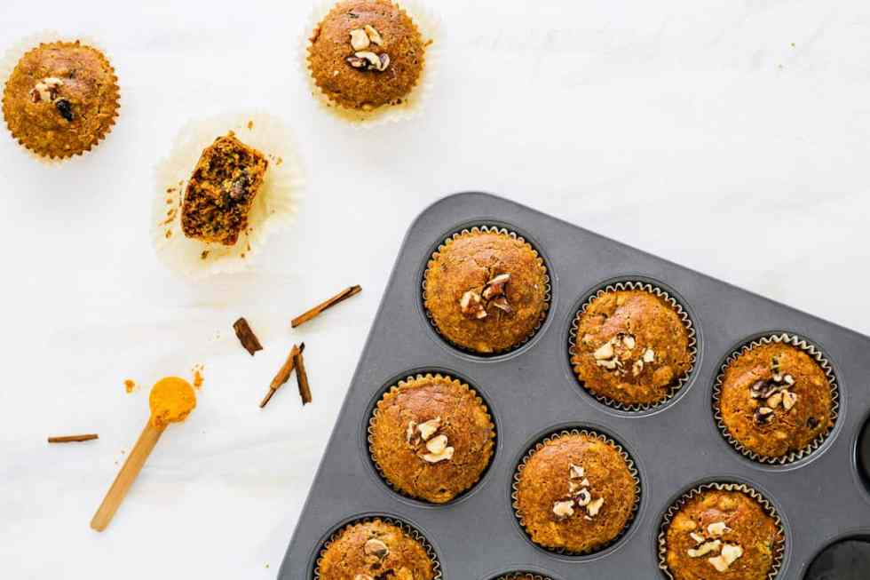 Overhead shot of gluten-free muffins in a muffin tin with spoonful of turmeric against shite backdrop.