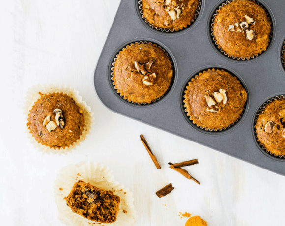 Muffin tin with gluten-free golden milk muffins against a white backdrop and a spoonful of turmeric.