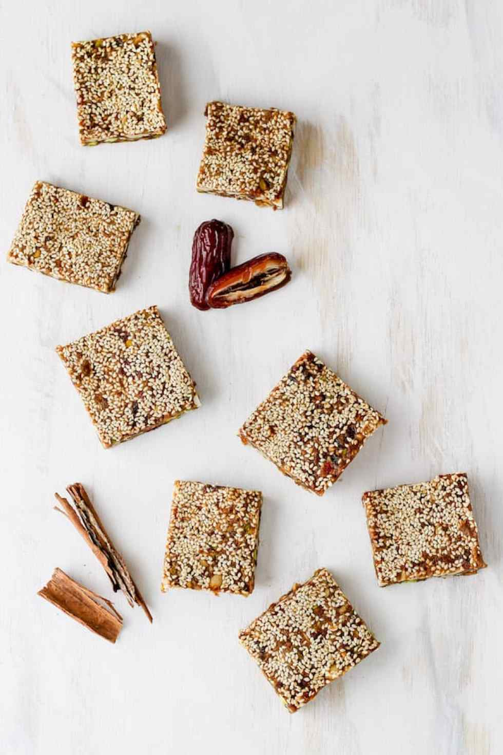 Overhead shot of sesame date bars arranged on a white backdrop with cinnamon sticks and date.