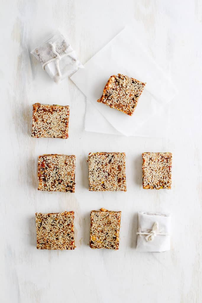 Sesame date bars arranged in rows with some wrapped in parchment paper nad tied with string. Set against white backdrop.